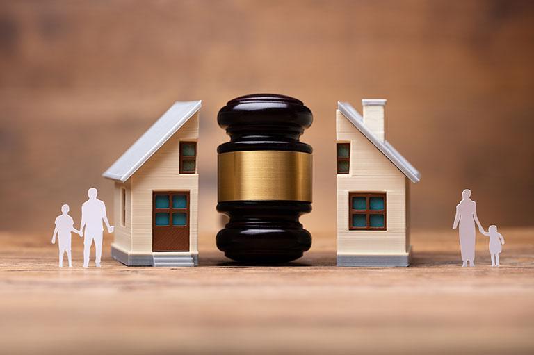 Młotek sądowy przedzielający figurkę domu